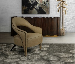 A strong design armchair upholstered in twill, a brass floor lamp, a wood sideboard, a grey rug, and a brass chandelier compose an apartment fierce interior design.