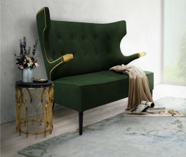 A green velvet mid century modern 2 seat sofa, a black and gold side table, a brass chandelier and a blue patterned hand tufted rug compose the ideal reception ambience décor of an office.
