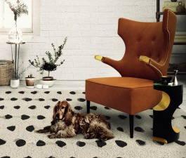 BA wingback orange velvet armchair with a matching black and gold side table, a modern bookcase and a black and white hand tufted rug compose this reading corner set in this modern living room.