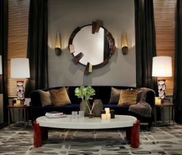 A modern living room décor with a blue velvet sofa, a marble coffee table and a large wall mirror, supported by two brass wall lamps and two table lamps on two glass top side tables. A walnut sideboar