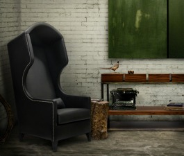 A black leather bonnet armchair with a small side table and a console table with drawers, composing a modern apartment living room décor.