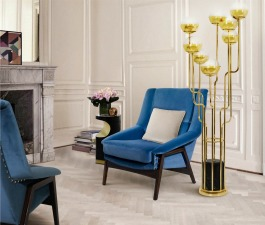A mid century living room with blue velvet armchairs, a brass and marble floor lamp and a small black side table. Elegant living room furniture pieces that create a unique and special set.