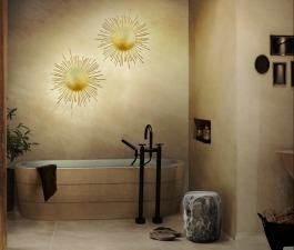 A marble stool imposes itself on the entrance of a modern bathroom. The sun shaped brass wall lamps soften this bathroom décor with the light it projects, creating a dramatic ambiance.