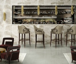A modern lounge area decoration of a hospitality project, with counter bar stools in velvet and brass pendant lights at the bar area. The velvet armchair is in marsala color tone and the round center