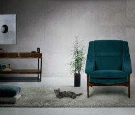 An urban and contemporary décor with a modern blue velvet armchair, a grey toned rug and a wood sideboard with many drawers.