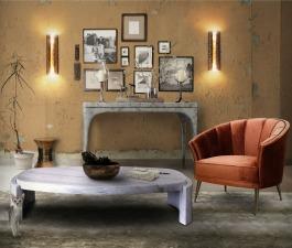 A rustic living room décor with custom made furniture pieces: an oval marble coffee table, a velvet armchair and modern wall sconces.